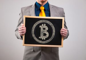 Businessman holding a board with bitcoin symbol and isolated on grey background